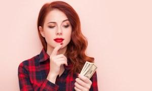 Frau hält Geldscheine in der Hand und überlegt