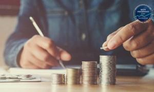 Mann stapelt Geldmuenzen auf einem Tisch