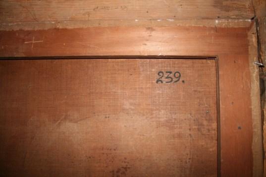 Reverso de obra con número de inventario pintado en el lienzo.