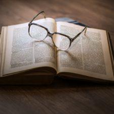 Eyeglasses on open book Paul Craig Roberts