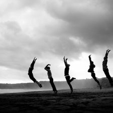 Black and white image of women stretching on beach - Women's Retirement Risks