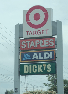 Retail signs arranged so that stores are shown in this order: Target, Staples, Aldi Dicks