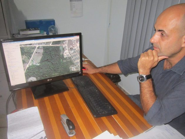 Pedro Correa, director of the environment in the Paranaita city government, looks at a photo of the city surrounded by forests, on his computer screen. Originally from the southern state of São Paulo, he worked for a few months on the construction of the Teles Pires hydropower dam and decided to stay in this town because he likes the quality of life. Credit: Mario Osava/IPS