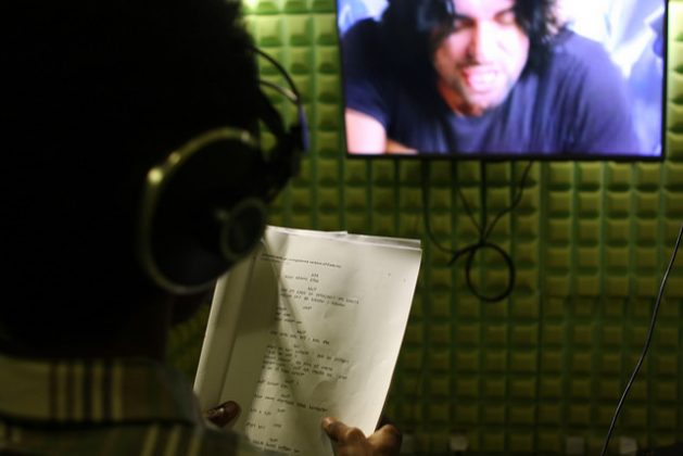One of KANA TV's dubbing team in a specially equipped sound-proof studio reading from his Amharic script to dub over a Turkish actor. Credit: James Jeffrey/IPS
