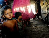 Children of families displaced by the 2004 Asian tsunami stand inside their tin-roofed shelter in the coastal town of Kalmunai. / Credit:Amantha Perera/IPS
