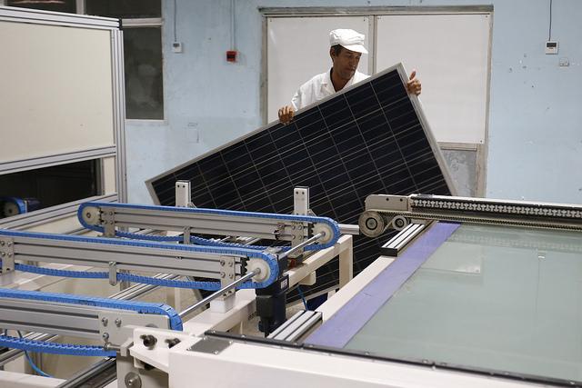 """Un trabajador manipula un panel solar en la planta de ensamblaje de la Empresa de Componentes Electrónicos """"Ernesto Che Guevara"""", en la occidental provincia de Pinar del Río, en Cuba. Crédito: Jorge Luis Baños/IPS"""
