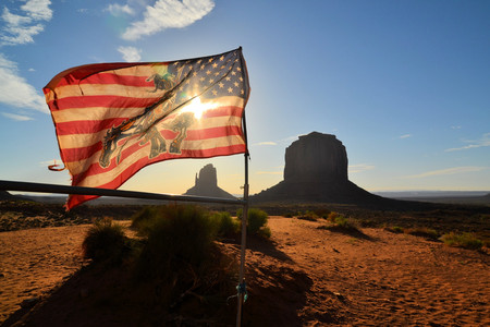 U.S. Flag at Monument Valley. The valley lies within the range of the Navajo Nation Reservation and is accessible from U.S. Highway 163.