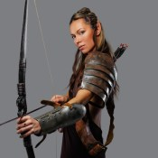 Elf woman in armour with bow isolated on a grey background.
