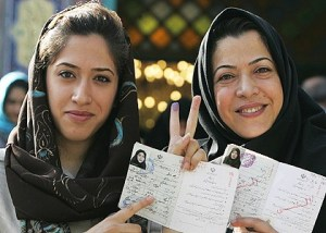 Two Iranian women show their inked fingers and the stamp on their identity cards showing that they have voted.