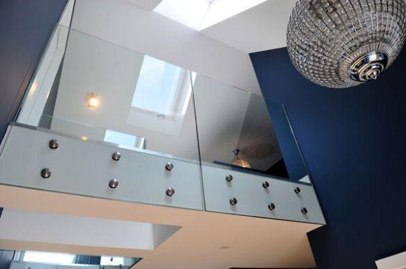 Hallway and upper-floor glass balconies. Sections of glass floor in walkways to bedrooms.
