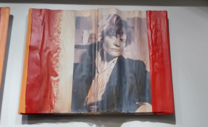 An open book bearing Iris Murdoch's image.