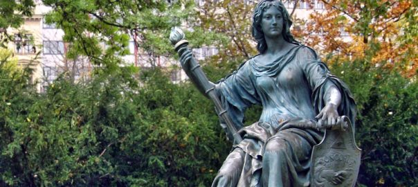 "Allegoric statue of ""Tolerance"", depicted as a seated woman with a torch in her right hand, and a shield on her left with the words ""Concordia religionum"" (harmony in religions)."