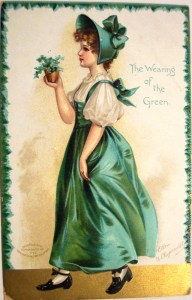 A girl in a green pinafore carries a pot of shamrock. Card message: The Wearing of the Green.
