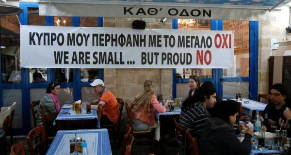 """People eat at a restaurant under a banner placed by the owner in central Nicosia. The banner reads: """"My proud Cyprus with the big No."""""""