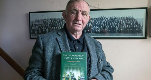 Jimmy Wren, who has written a book, The GPO Garrison Easter Week 1916, at his home in Donnycarney. On the wall is a group photograph of Rising participants,  taken in 1936. Photograph: Dave Meehan