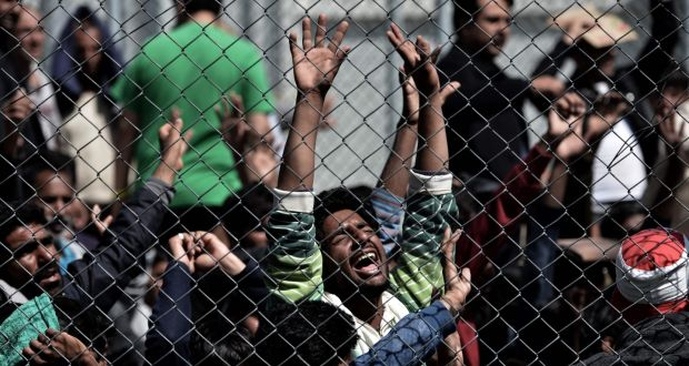 A man holds his hands up behind a chain link fence as Pakistani and Afghan migrants protest inside the Moria detention centre in Mytilene on the Greek island of Lesbos on Tuesday  against deportation to Turkey.  Photograph: Aris Messinis/AFP/Getty Images