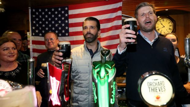 Donald Trump jnr (centre), and Eric Trump (right) behind the bar in Tubridy's Bar in the village of Doonbeg, Co Clare. Photograph: Brian Lawless/PA Wire