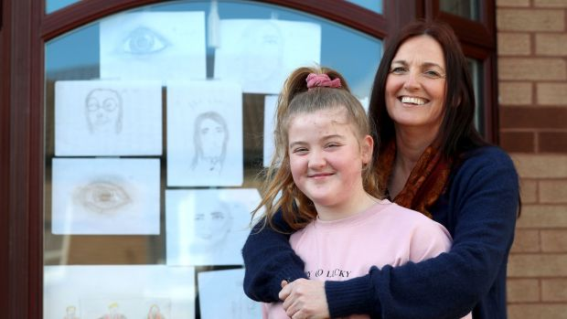 Ellen Cahill, organisatrice d'un groupe communautaire dans le domaine de Ballymurphy, à Belfast, avec sa fille Aoibhe et quelques-unes des photos que les enfants locaux ont dessinées à placer dans les fenêtres avant de leurs maisons pour égayer leur quartier. Photographie: Stephen Davison