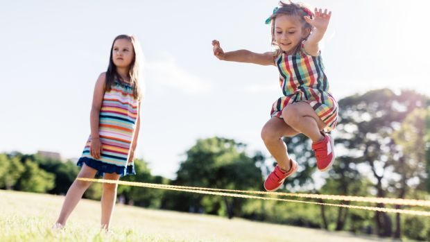 Little girl in a colorful dress jumping through the elastic. Childhood game. Chinese jumping rope.
