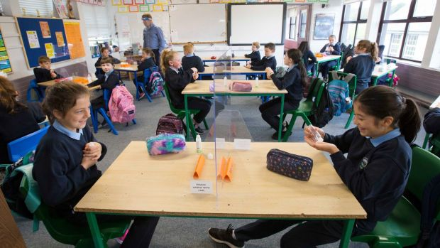 Mona Lowe (right) uses her bottle of hand sanitsier in class. Photograph: Brian Farrell/The Irish Times
