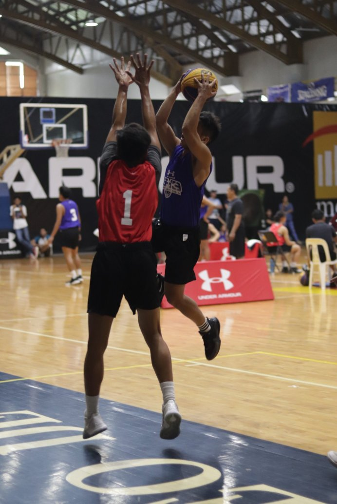 UA 3x3 Basketball participant attacks the rim with a jump shot while being blocked