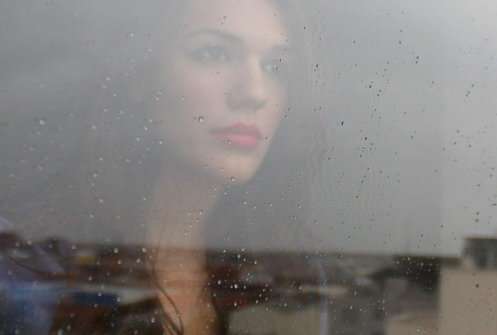 femme triste derrière sa fenêtre