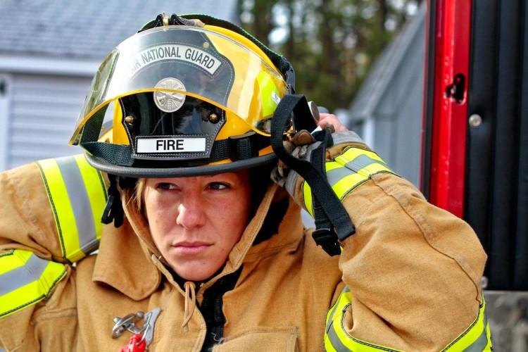 Femme pompière déjà vêtue de son vêtement ignifuge enfilant son casque