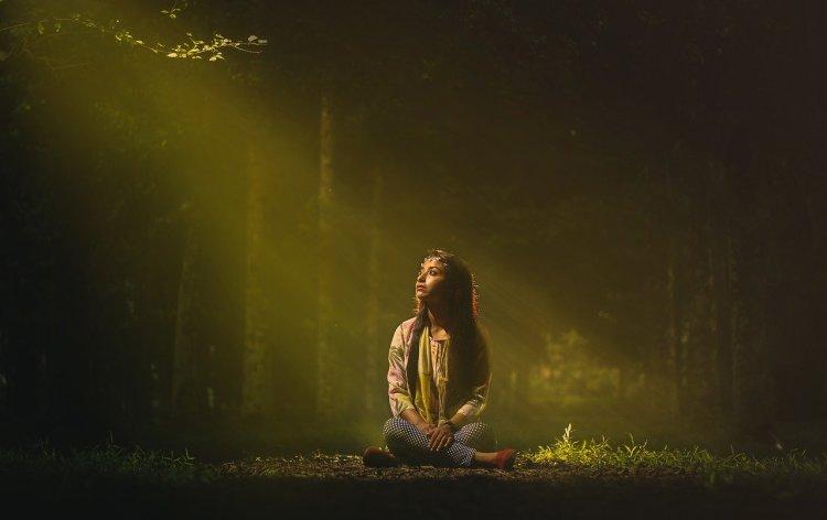 Une femme fixe du regard le premier rayon de lumière au matin et l'environnement se révèle à elle.