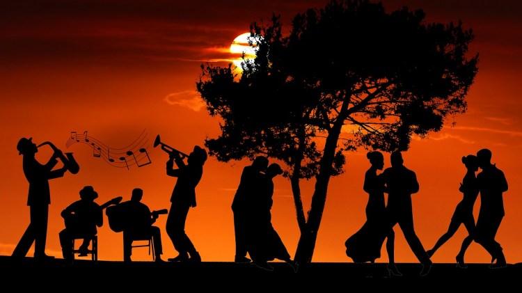 Des musiciens et des danseurs de tout âge dansent au soleil couchant.