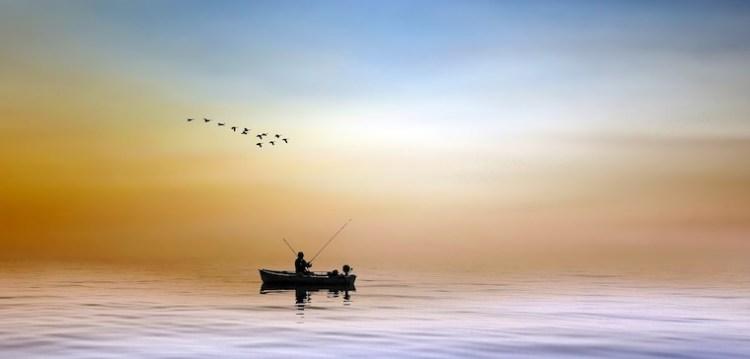 Un pêcheur, seul dans sa barque à l'aurore, un moment de grand calme et d'attention.