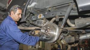 Thalal Khalaf, a new Canadian from Syria, is repairing a car at MacPhee autoshop in Dartmouth Monday