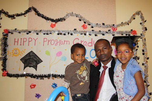 Father with son and daughter in front of graduation sign