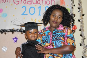 Mom and son in front of graduation sign