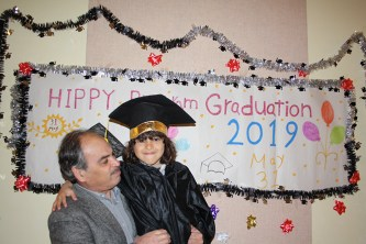 Father and daughter in front of graduation sign