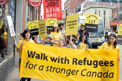 People carrying the Walk with Refugees banner and signs