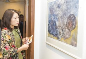 A visitor taking keen interest in the art exhibit by Pakistan women artists.