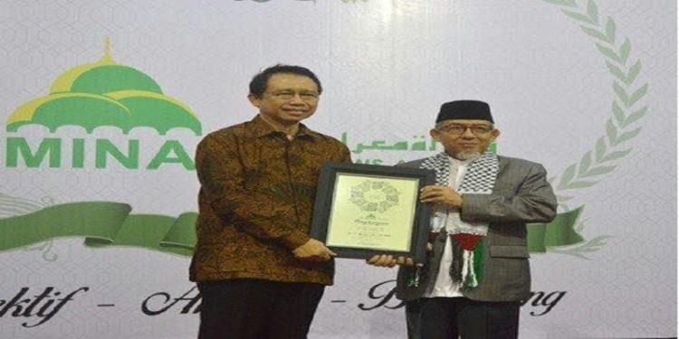 Ketua DPR RI periode 2009-2014 Marzuki Alie (kiri) menerima penghargaan dari MINA yang diserahkan oleh Komisaris MINA, KH Yakhsyallah Mansur (kanan). Foto: Tommy/Islampos