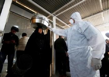 Tim medis memeriksa suhu penumpang di Lintas Perbatasan Shalamcha antara Irak dan Iran. Foto: Reuters