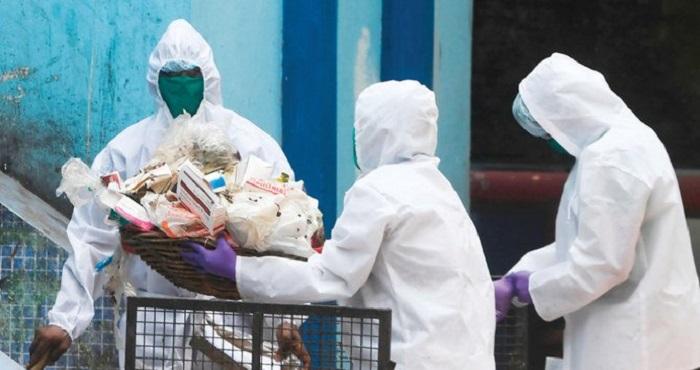 Pekerja kota mengumpulkan limbah dari rumah sakit pemerintah selama penutupan nasional sebagai tindakan pencegahan terhadap COVID-19 di Kolkata, India. Foto: AFP