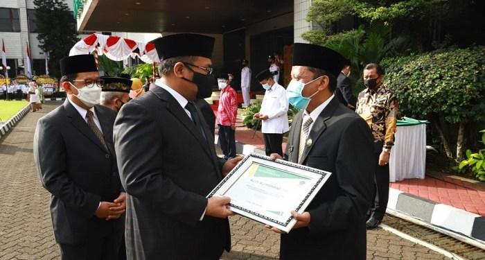 Menteri Agama Yaqut Cholil Qoumas menyerahkan penghargaan kepada Budi Ali Hidayat. Foto: Kemenag