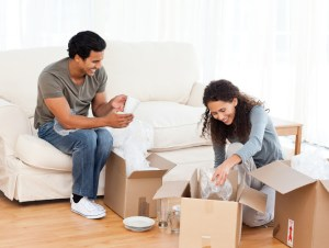 Happy couple packing glasses together in the living-room for their removal