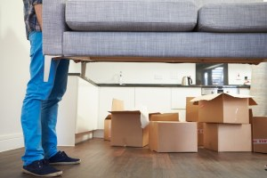 Close Up Of Man Carrying Sofa As He Moves Into New Home