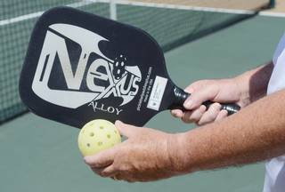 Sun City's Rick Wright holds a pickleball paddle and a hollow, light-weight pickleball.