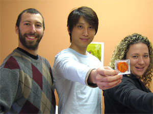 group of two males and one female holding an orange condom