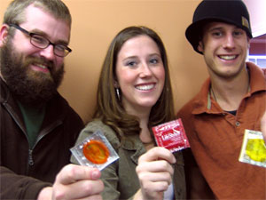 Two young males and a young female hold condoms