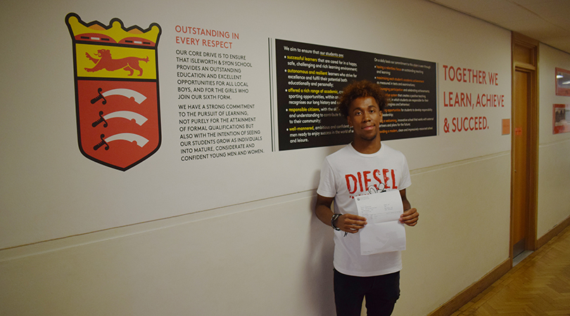 Student Diallo Williams stands holding a piece of paper holding his results. He is standing in a corridor in front of the Isleworth & Syon crest and mission statement.