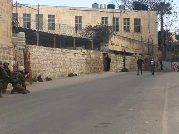 An Israeli soldier aims his rifle at Palestinians making their way past the boys' school