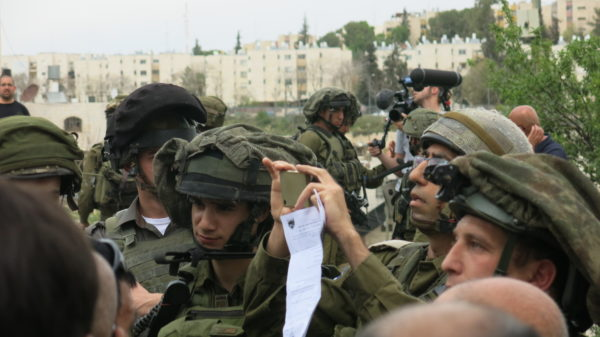 An Israeli soldier films demonstrators whilst holding a piece of paper declaring the area a Closed Military Zone during the Land Day action in al-Khalil. This image was taken an hour after the arrests made that day.