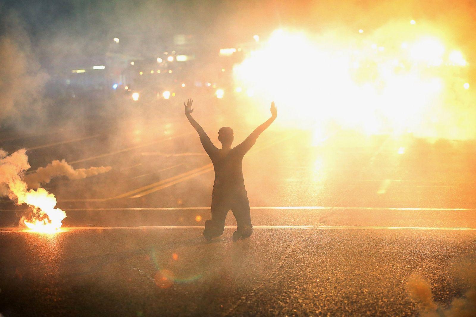 El gas lacrimógeno rodea a una mujer arrodillada en la calle con las manos en alto después de una protesta por Michael Brown, el 17 de agosto de 2014, en Ferguson, Missouri. Fotografía: Scott Olson/Getty Images