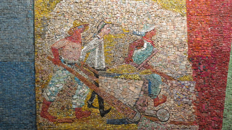 Nahum Gutman's Mosaic Wall - wheel barrow boys.  The new immigrant has no tan. One has taken off his shirt showing his untanned body.